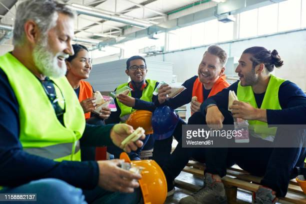 happy workers in factory having lunch break together - lunch break stock pictures, royalty-free photos & images