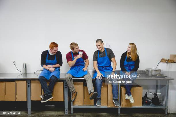 happy workers talking while sitting on table in cashew factory - plant stock pictures, royalty-free photos & images