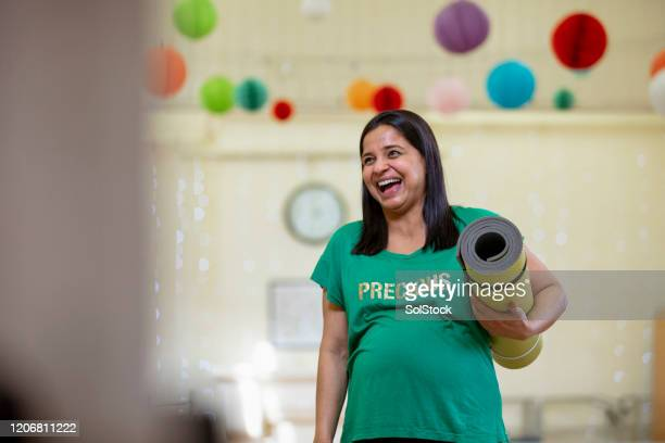 happy yoga teacher in bright room - pregnancy stock pictures, royalty-free photos & images