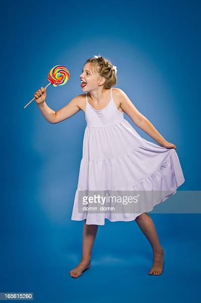 Happy, young 9 years girl with multicoloured lollipop on blue