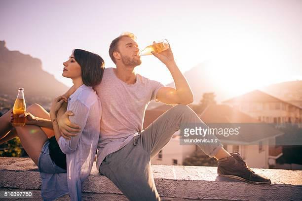 Glückliche junge Erwachsene paar Datierung auf der Dachterrasse ein Sonnenuntergang