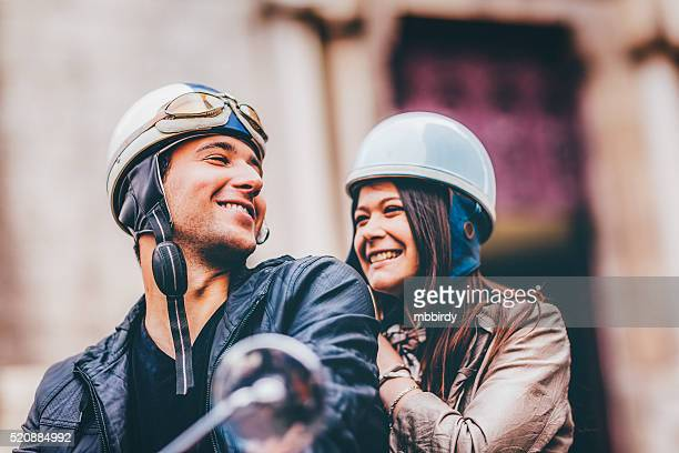 Happy young adult couple in love on scooters