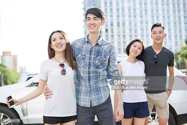 Happy young adults and car