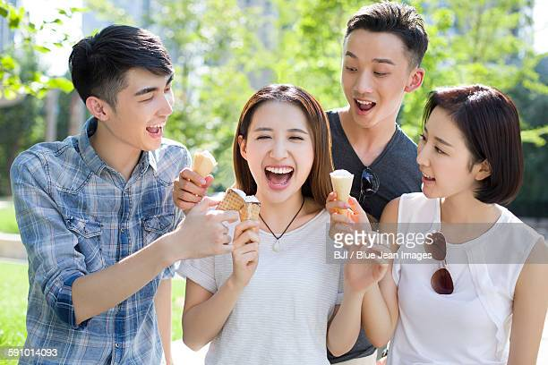 Happy young adults eating ice cream