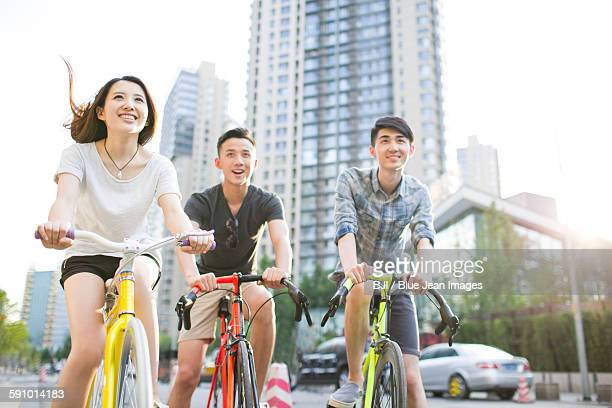 Happy young adults riding bicycles