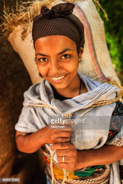 Happy young African woman carrying straw, East Africa