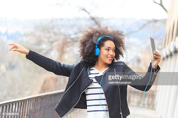 Happy young african woman listening music on street
