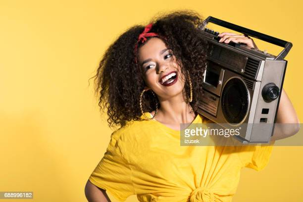 Happy young afro woman holding boombox
