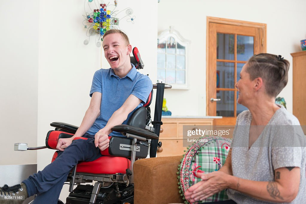 Happy young ALS patient with his mom : Stock Photo