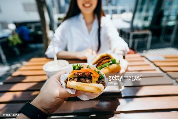 happy young asian couple eating beef burger with fries in an outdoor fast food restaurant - burger menselijke rol stockfoto's en -beelden