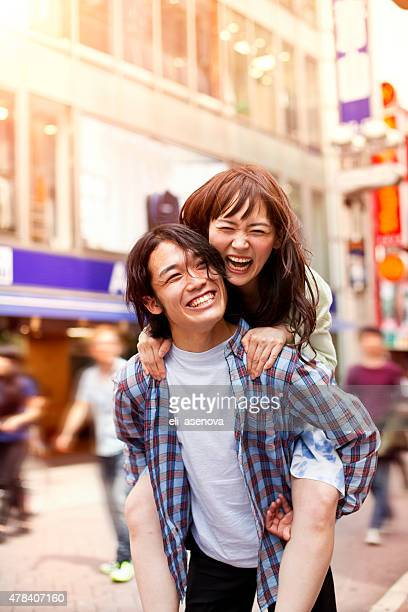 Happy young asian couple having fun with piggy back