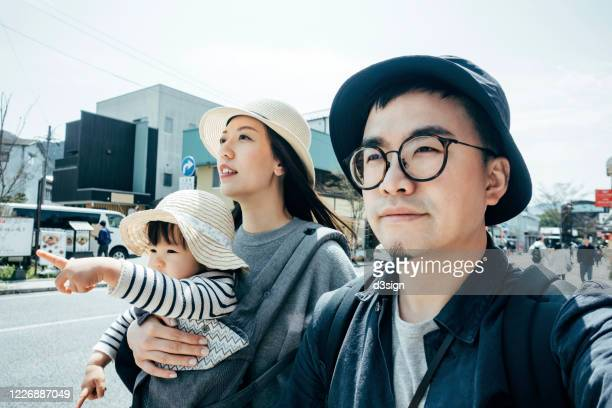 happy young asian family of three on a trip visiting and exploring a local town in fukuoka, japan on a sunny day - travel ストックフォトと画像