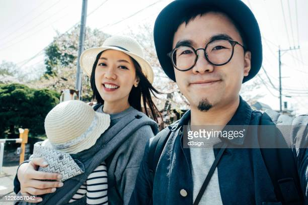 happy young asian family of three taking a selfie, smiling happily while on a trip visiting and exploring a local town in fukuoka, japan on a sunny day - 両親 ストックフォトと画像