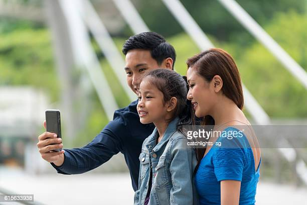 Happy Young Asian Family Taking a Wefie