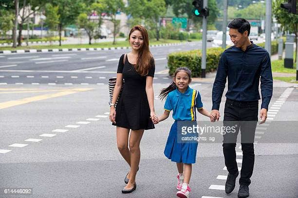 Happy Young Asian Family Walking on Pedestrian Crossing