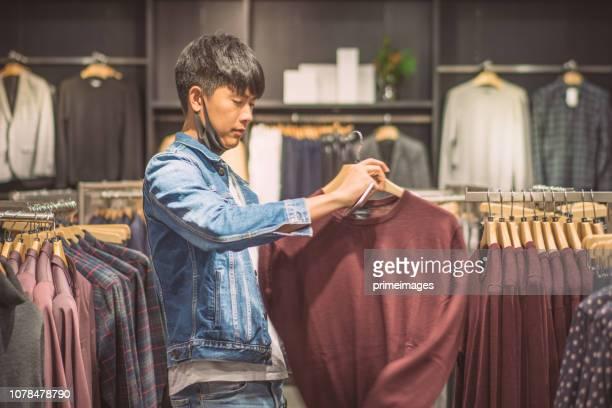 シャツ モールや衣類で選ぶジャケットの幸せな若いアジア人男性が日本に格納します。 - メンズウェア ストックフォトと画像