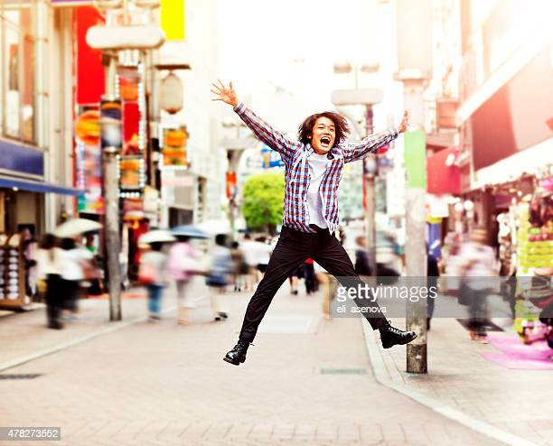 Happy young asian man jumping in Shibuya on the street