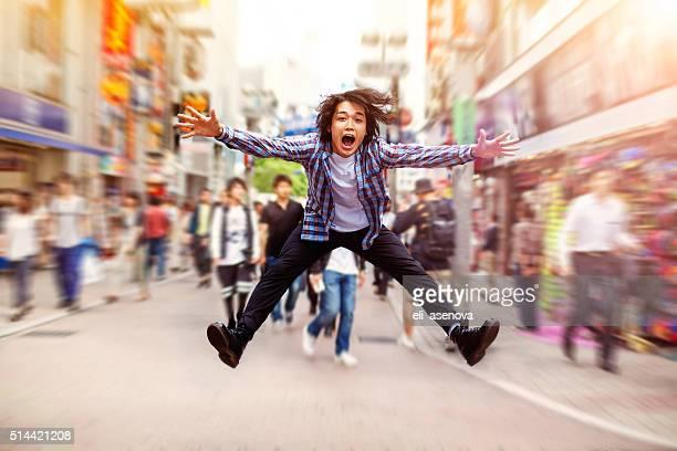 幸せな若いアジア人男性ジャンプ渋谷、ストリート