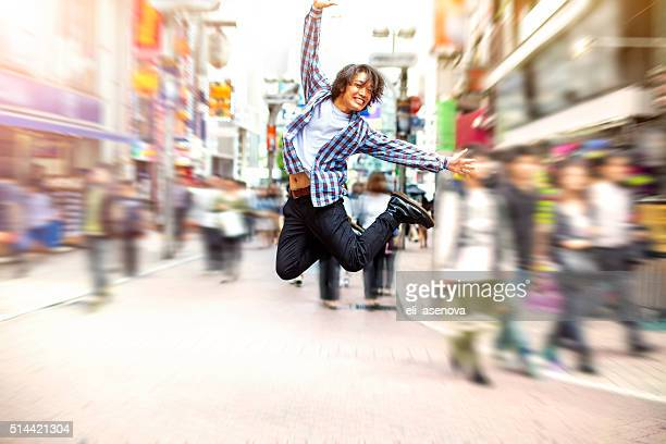 happy young asian man jumping in shibuya on the street - men's field event stock pictures, royalty-free photos & images