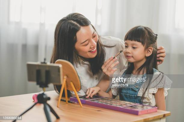 happy young asian mother and her daughter recording video blog at home with makeup theme - kids makeup stock pictures, royalty-free photos & images