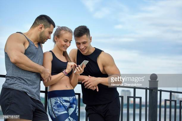 Happy young athletes using mobile phone while leaning by railing