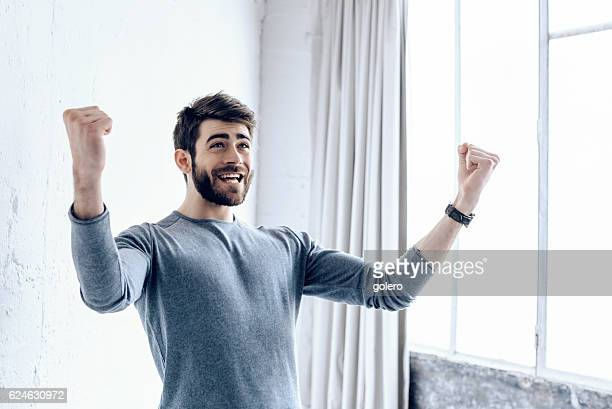 happy young bearded man cheering  in paris loft appartment - extatisch stockfoto's en -beelden