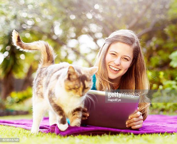 Happy young beauty in garden with cat and digital tablet