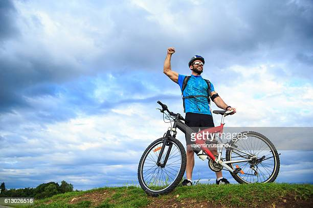 Happy young biker standing hand up on top mountain