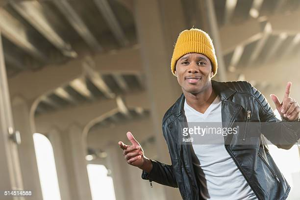 Happy young black man in city wearing yellow beanie