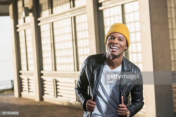 happy young black man in city wearing yellow beanie - black jacket stock pictures, royalty-free photos & images