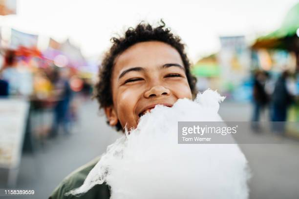 happy young boy eating candy floss - cotton candy stock pictures, royalty-free photos & images
