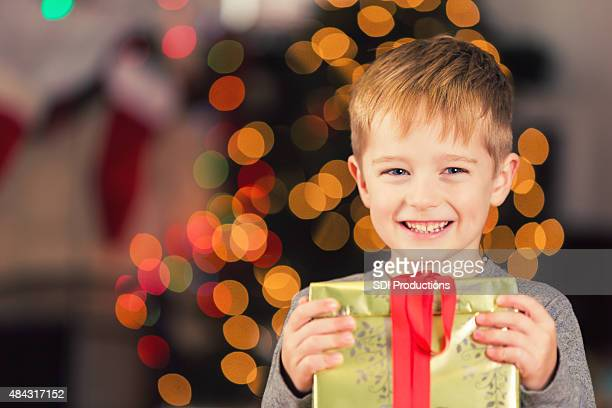 Happy young boy holding Christmas gift near decorated tree