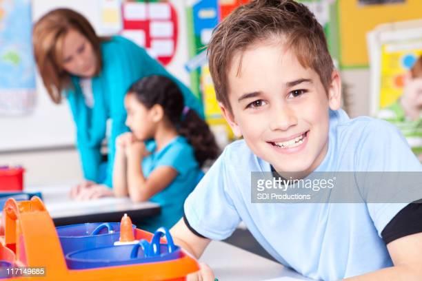 Happy Young Boy in Classroom at School