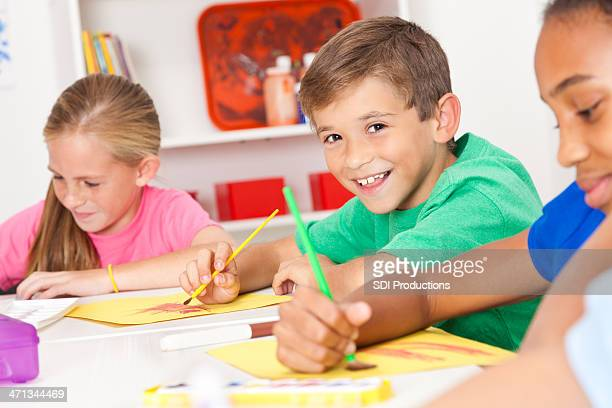 Happy young boy in his art class