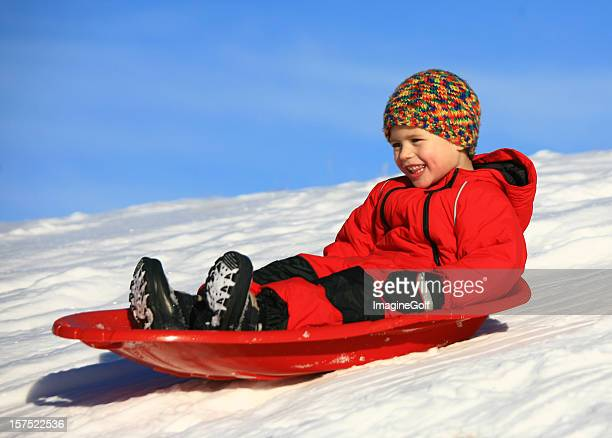happy young boy sledding - snow boot stock photos and pictures