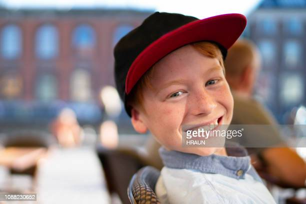 Happy young boy with a baseball cab on a restaurant.