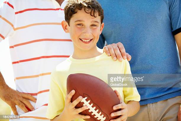 Heureux jeune garçon avec ballon de football