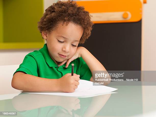 Happy young boy writing on sheet of paper, blackboard in background