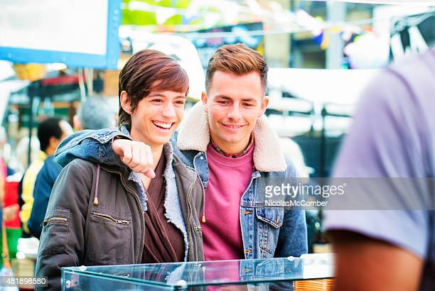 Happy young British couple visiting Autumn market in London UK