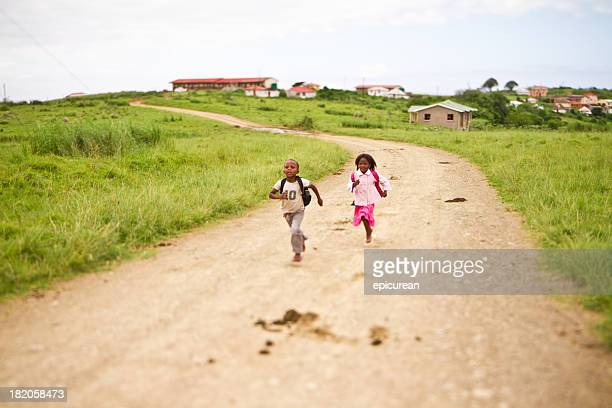 Happy young brother and sister running to school together