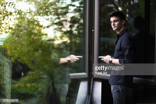 happy young business man texting in front of the window - business finance and industry stock pictures, royalty-free photos & images