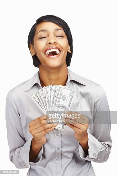 Happy young business woman holding currency notes against white