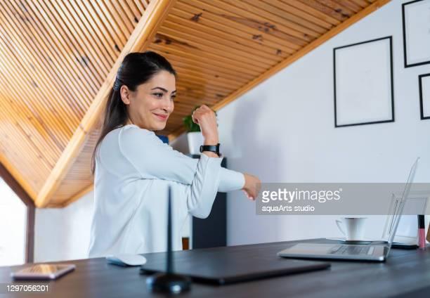 幸せな若いビジネスウーマンは、自宅のオフィスでストレッチエクササイズや練習をしています。 - 人間工学 ストックフォトと画像