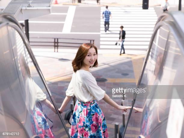 エスカレーター上の肩越しに見て幸せな若いビジネス女性 - looking over shoulder ストックフォトと画像