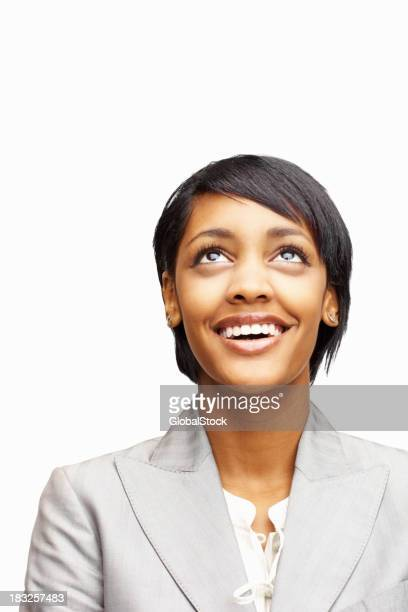 Happy young business woman looking up against white
