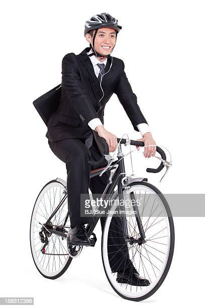 Happy young businessman cycling to work