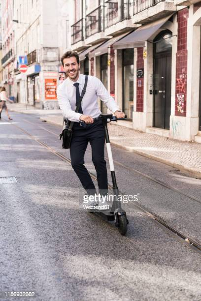 happy young businessman riding e-scooter in the city, lissabon, portugal - electric scooter stock pictures, royalty-free photos & images