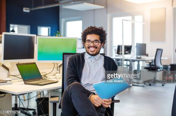 happy young businessman sitting at his desk - dreiviertelansicht stock-fotos und bilder