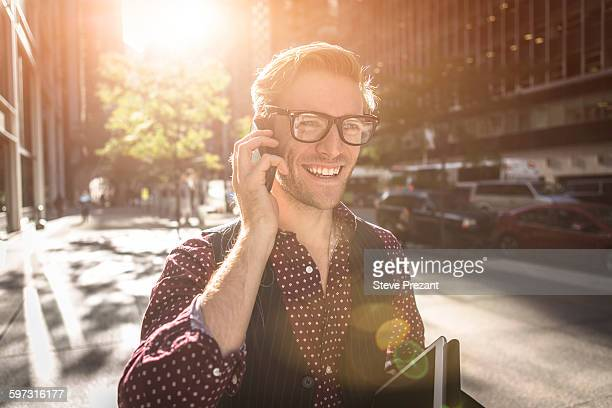 Happy young businessman strolling city street talking on smartphone, New York, USA