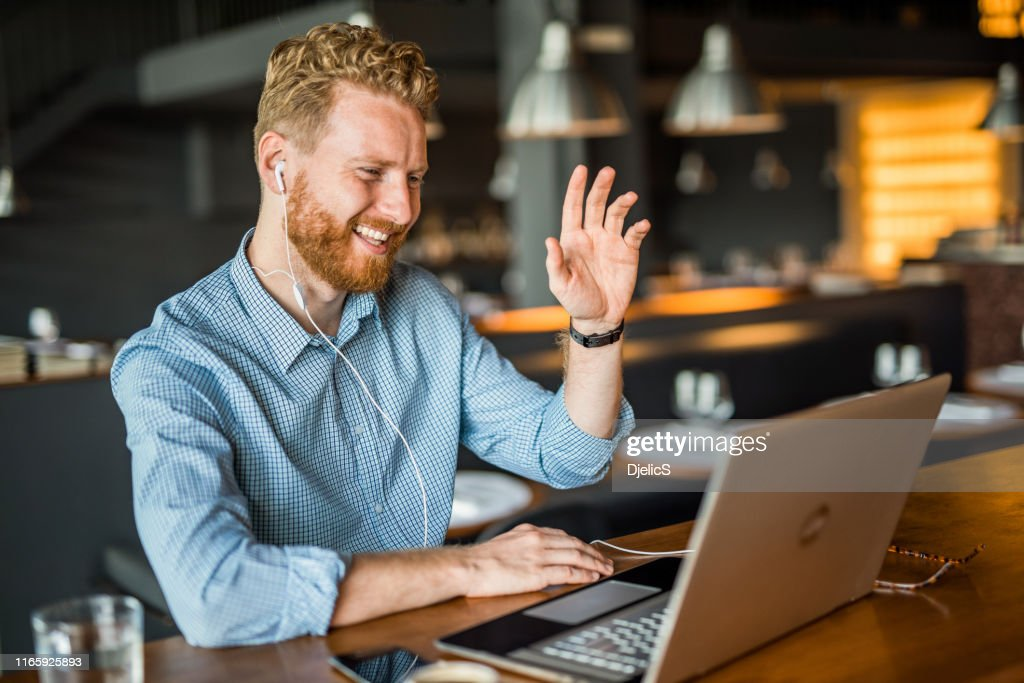 Happy young businessman waving to an online client. : Stock Photo